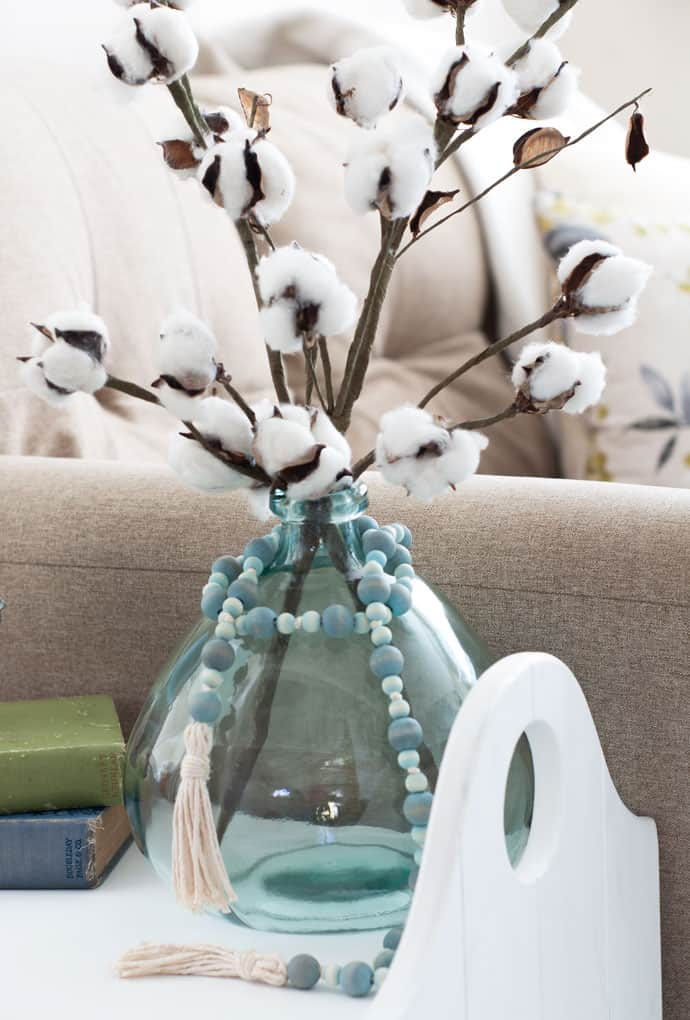 glass aqua jar with aqua beads and tassels and cotton stems on white table with books on the side and sofa with pillows in background