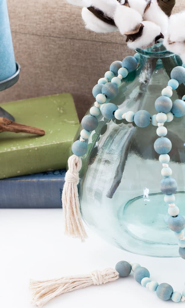 glass aqua jar with aqua beads and tassels on white table with books in background