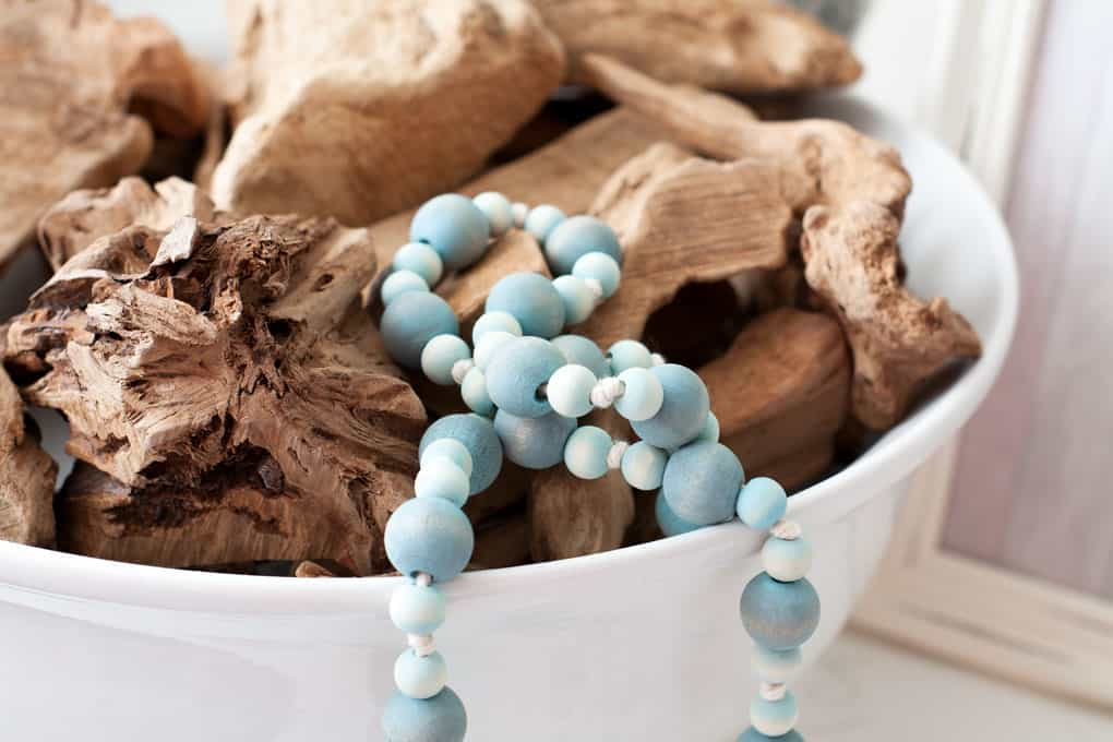 white bowl with driftwood and aqua wood bead garland