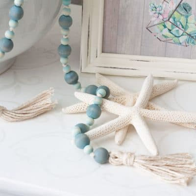 starfish with aqua wooden beads and tassels sitting on white table