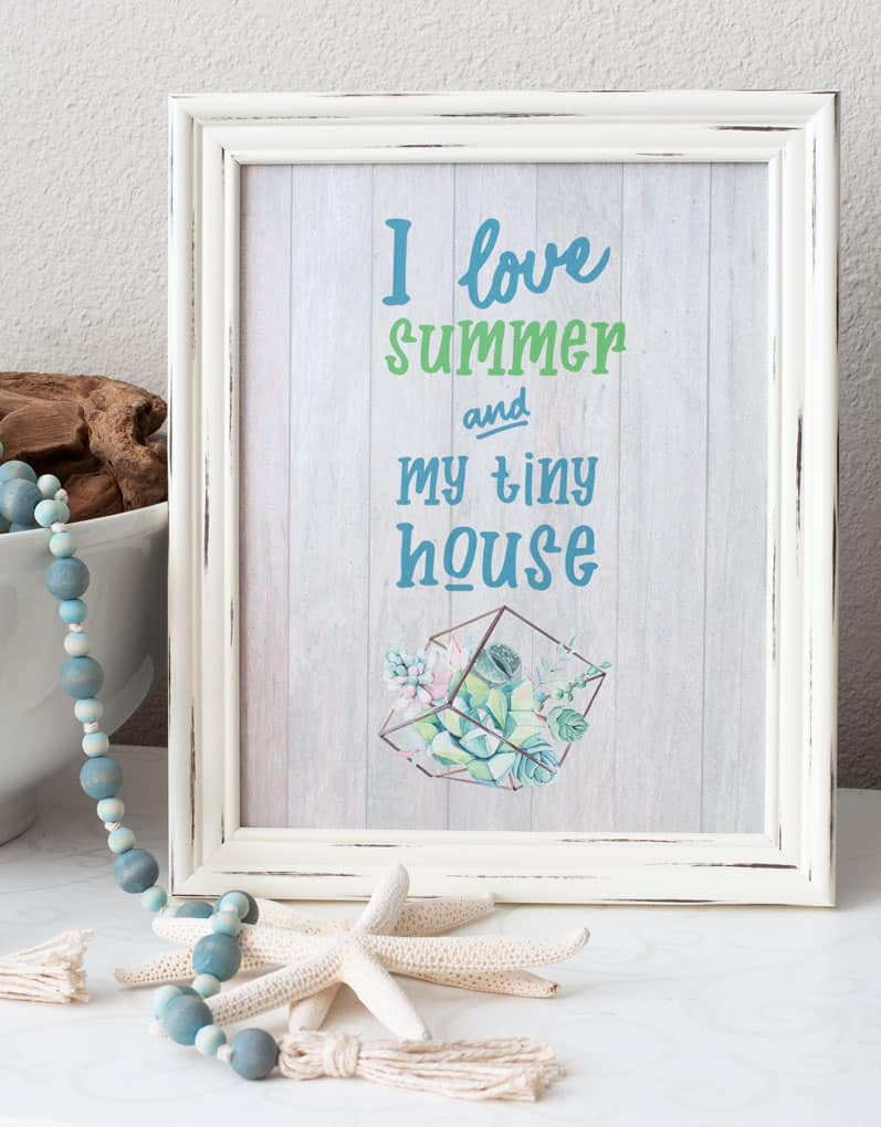 white frame with printable that says i love summer and my tiny house starfish white bowl with driftwood and aqua wood bead garland with tassels on white table