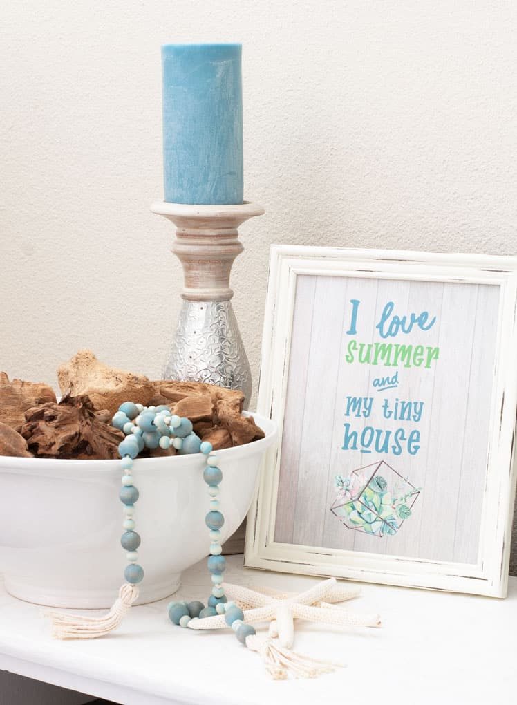 white frame with printable that says i love summer and my tiny house candle holder with aqua candle white bowl with driftwood and aqua wood bead garland with tassels on white table