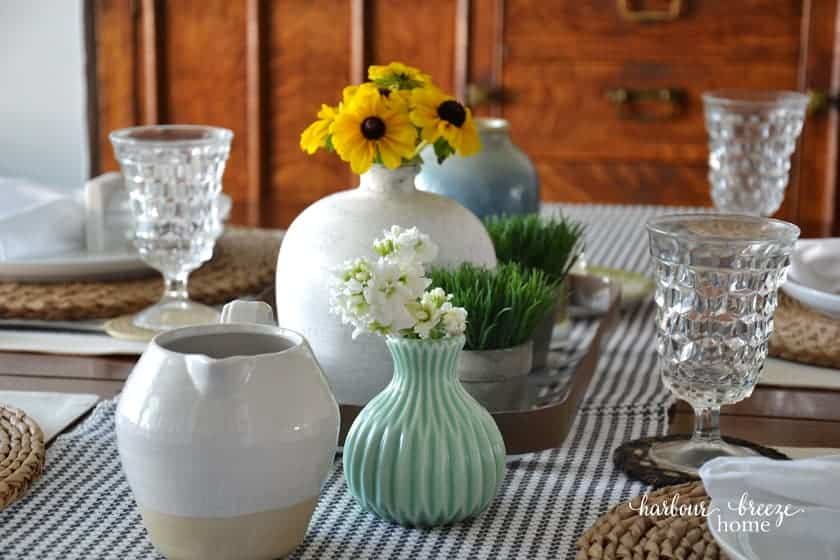 table with checkered tablecloth glasses vases and flowers