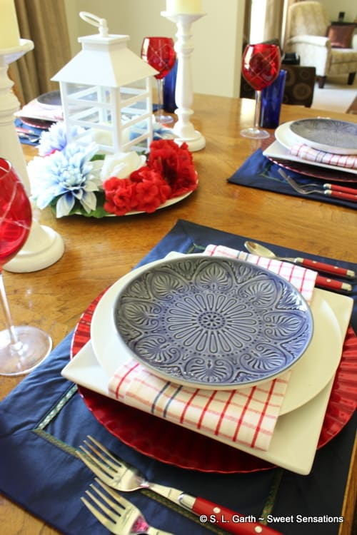 table setting in red white blue with plates napkins centerpiece placemats glasses silverware