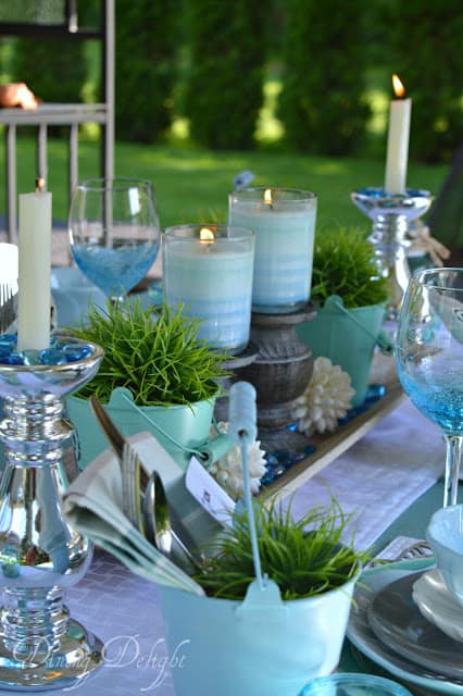 table setting in blues and aquas with plates napkins centerpiece placemats glasses silverware candles and plants