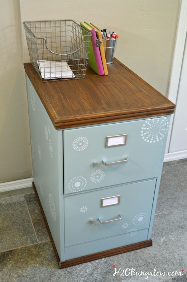 small filing cabinet with wood top in aqua with white stenciled print basket and office supplies sitting on top