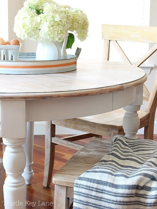 white farmhouse table and chair with tray and pitcher with flowers striped seat cushion