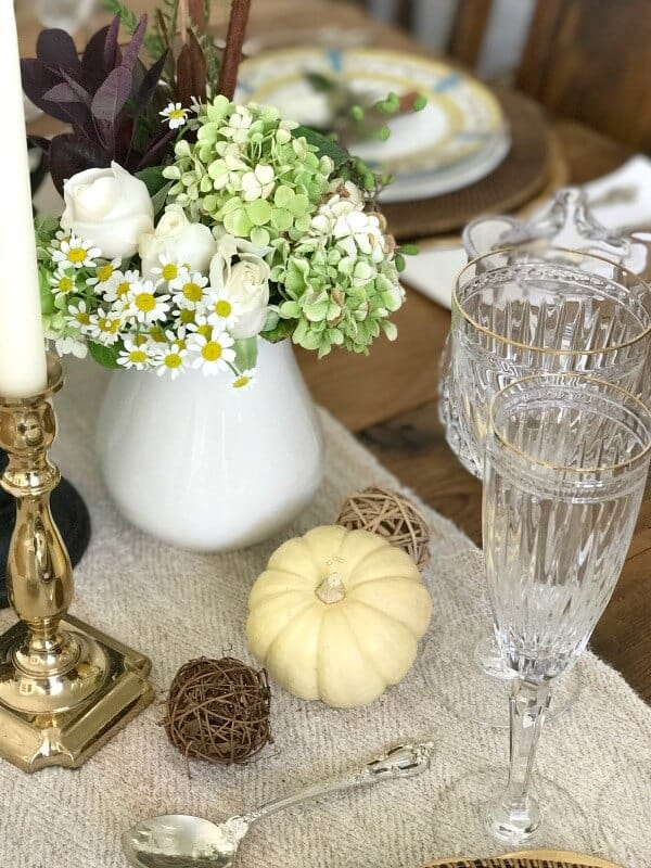 table with white pitcher and flowers pumpkin clear glasses brass candle holder white candle