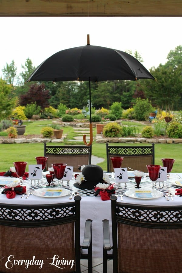 garden setting with tablescape setting with red white and black tableware all under a black umbrella