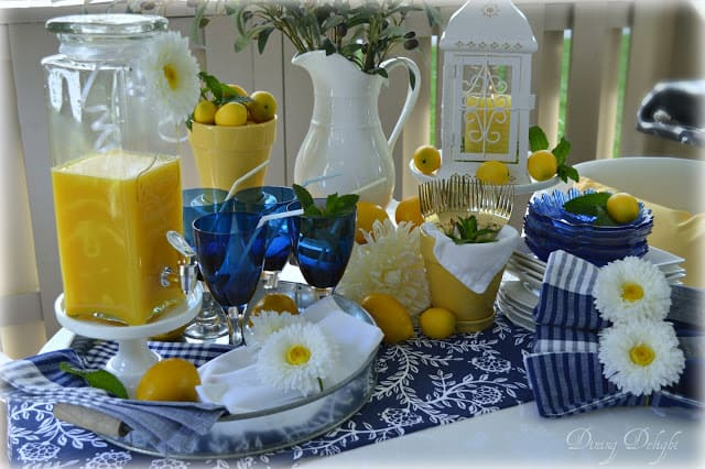 tablescape with blue white yellow tableware lemons white pitcher with foliage white daisies and blue glasses