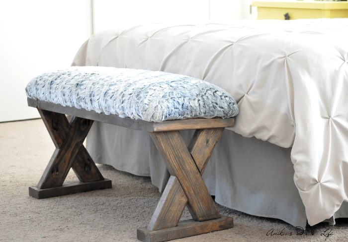 bed with bedding and bedskirt and farmhouse wooden bench with blue and white upholstery