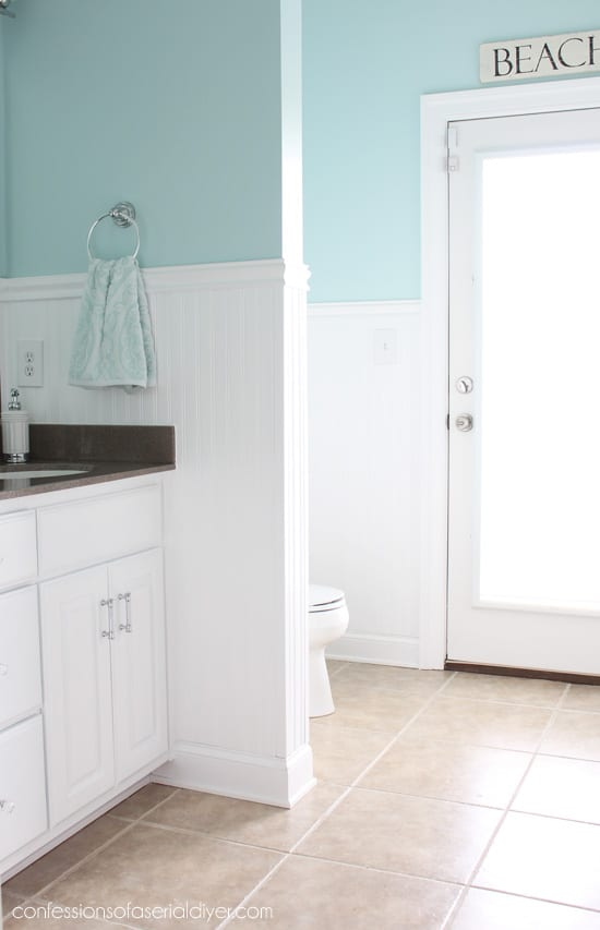 white aqua bathroom with bead board wainscot door and toilet in background vanity in foreground