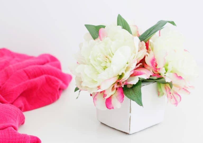 white chalkpaint vase with white pink flowers and pink blanket on white countertop