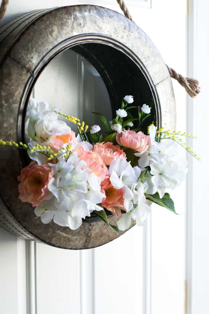galvanized tire with white and peach flowers used as door wreath