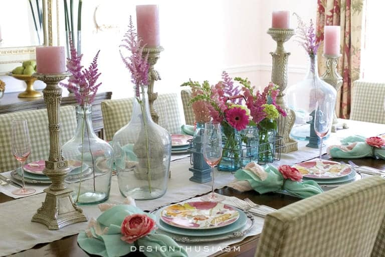 tablescape with summery pastel and bright colored dishes glasses flowers and tableware