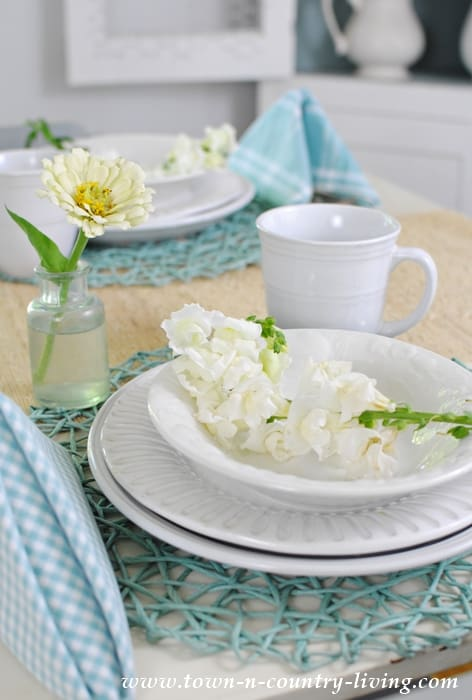 tablescape with white and blue dishes cups and linens with white and yellow flowers in vases