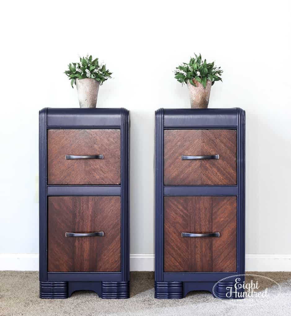 two nightstands painted navy with stained drawers and boxwoods on top of the nightstands