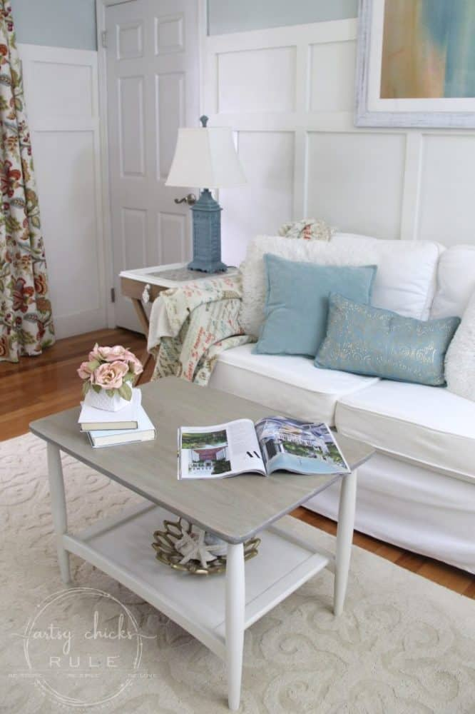 living area with white sofa aqua pillows white and gray coffee table with flower vase and books
