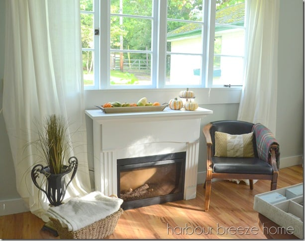 Tuesday turn about #7 fireplace in living room with chair and pillow window above fireplace looking outside