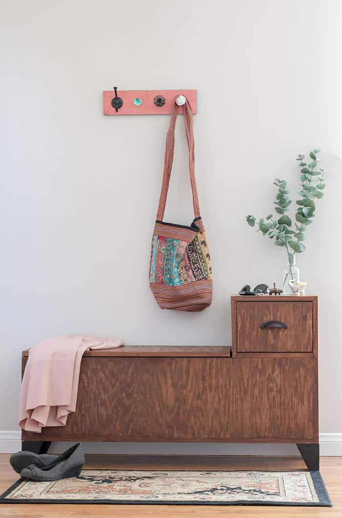 Tuesday turn about #7 storage bench styled with wall hooks and a tote vase with foliage