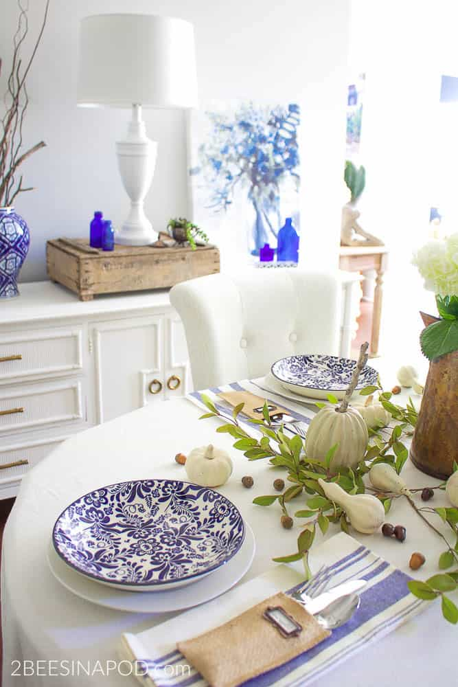 Tuesday turn about #7 tablescape with blue and white dishes and fall elements on a table with white tablecloth buffet in background with blue accessories