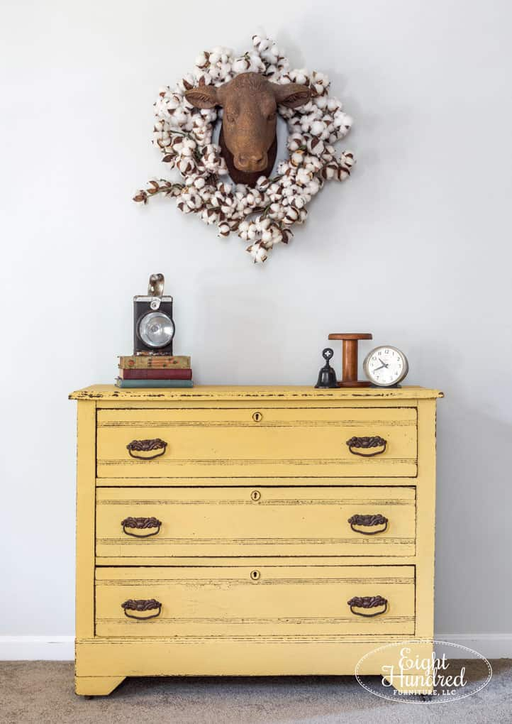 Tuesday turn about #7 yellow dresser with cows head hanging above and cotton stem wreath