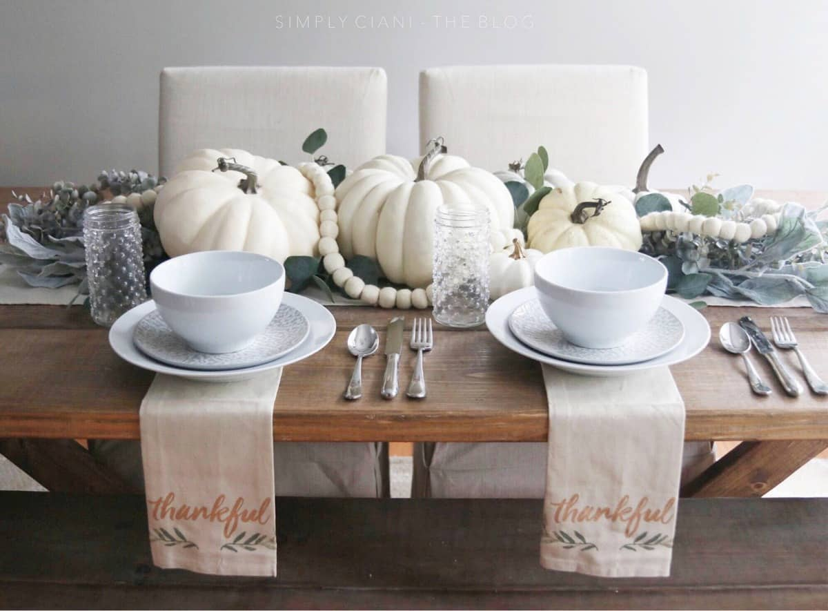 tuesday turn about 8 tablescape on rustic table with white pumpkins white dishes flatware and napkins with writing