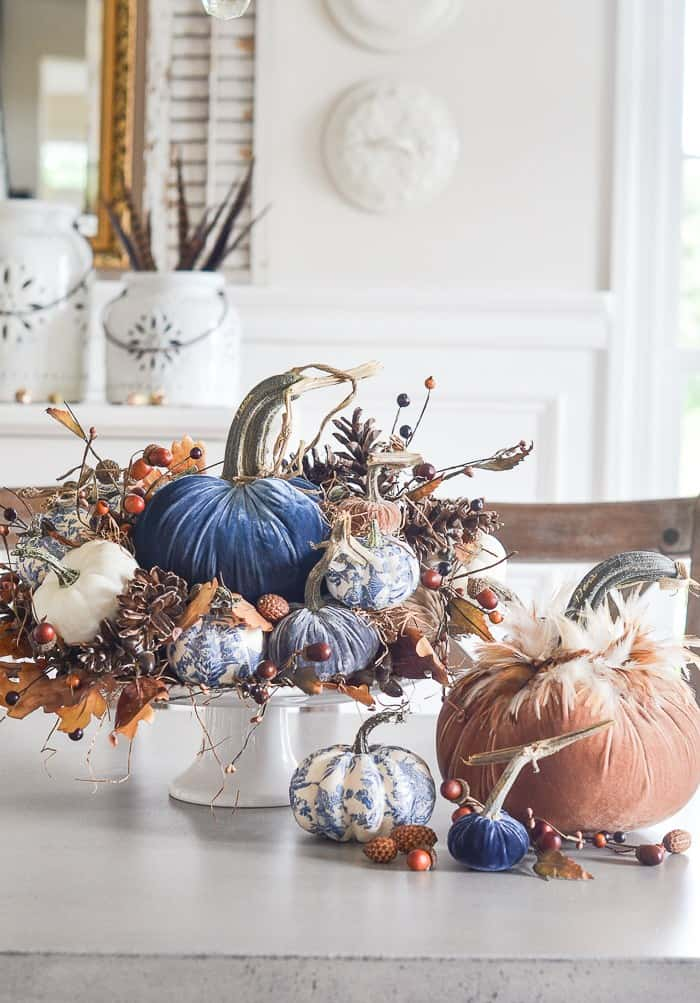 tuesday turn about 8 centerpiece with blue ivory orange and printed pumpkins with rustic fall elements of leaves acorns and bittersweet