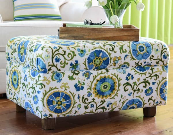 tuesday turn about 8 small ottoman covered in blue green yellow and white fabric with wooden tray on top