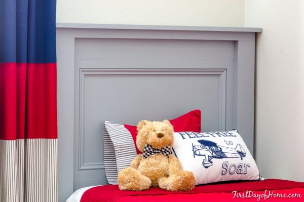 tuesday turn about 8 gray headboard in back of bed with red bedspread pillows and teddy bear