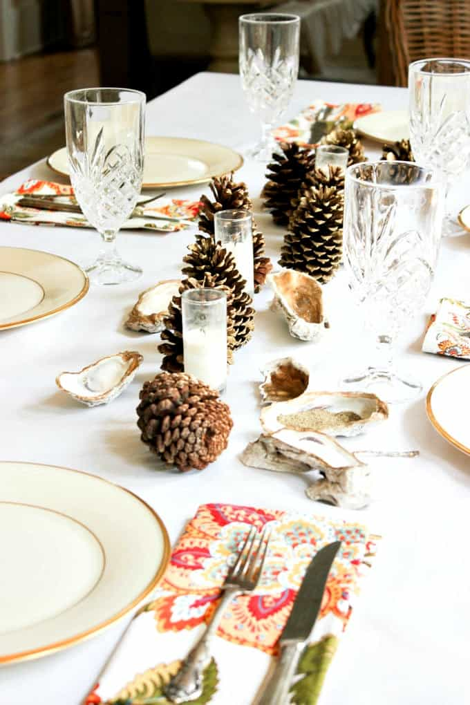 tuesday turn about 9 best blog diys tablescape with pine cones and oyster shells white plates with gold bands and clear stemware