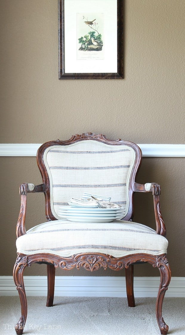 tuesday turn about 9 best blog diys french chair with striped linen fabric against tan wall and art hanging above with dishes sitting in chair