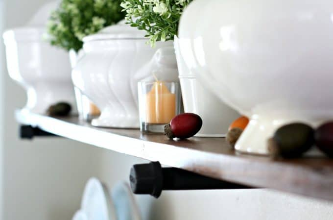 adding fall decor to a small kitchen open shelves with white dinnerware plants pumpkins and natural elements