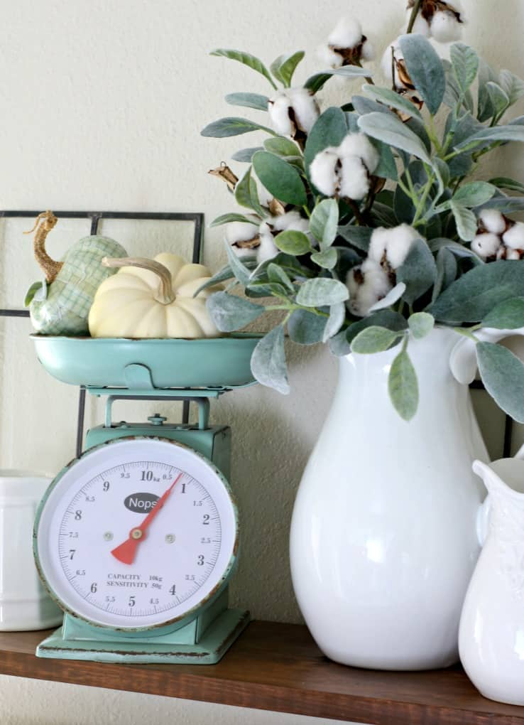 adding fall decor to a small kitchen open shelves with white dinnerware plants pumpkins and natural elements vintage scale cotton stems in pitcher