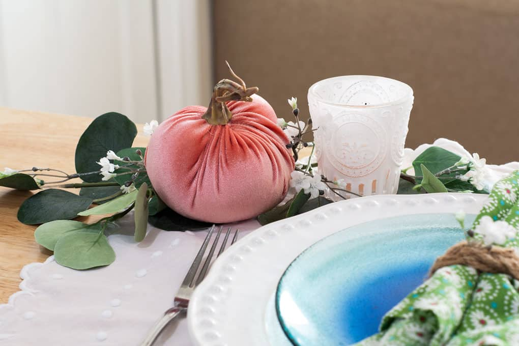 7 elements for a single fall tablescape table for one #2 table place setting with plates silverware pumpkin candle and foliage on a wood counter