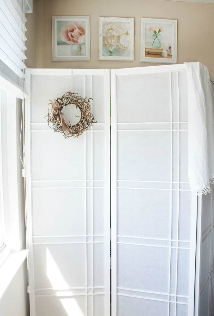 add quick and easy extra closet to any room room divider near window with floral photos in frames above on wall