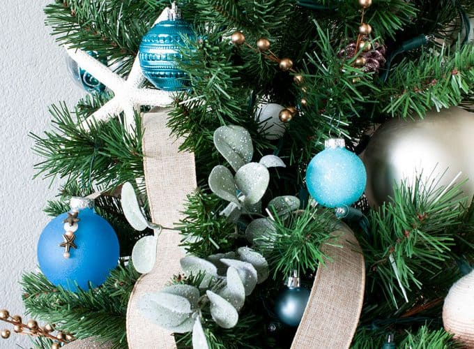 big ideas for decorating a small christmas tree with coastal ornaments and ribbon