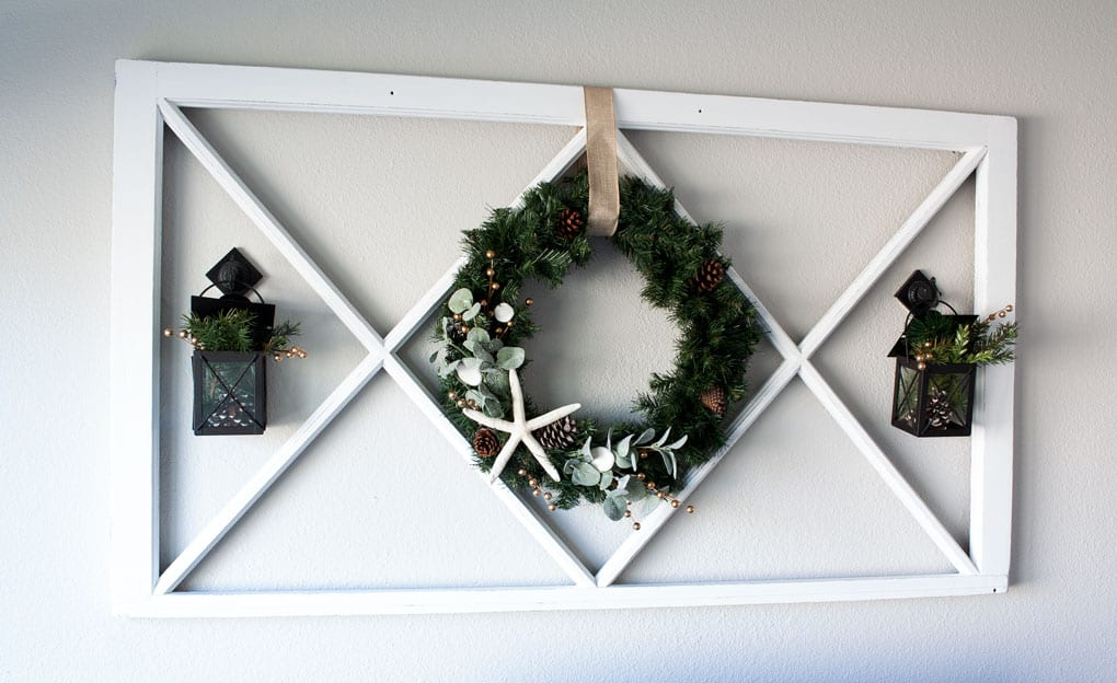 diy coastal farmhouse winter wreath on wall with window pane and lanterns