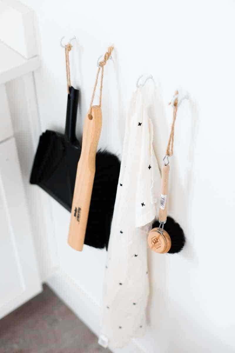homestyle gathering 3 cleaning tools hanging on hooks on white wall