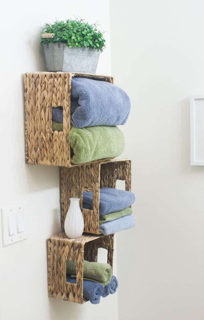 baskets mounted to wall with bath towels and decor