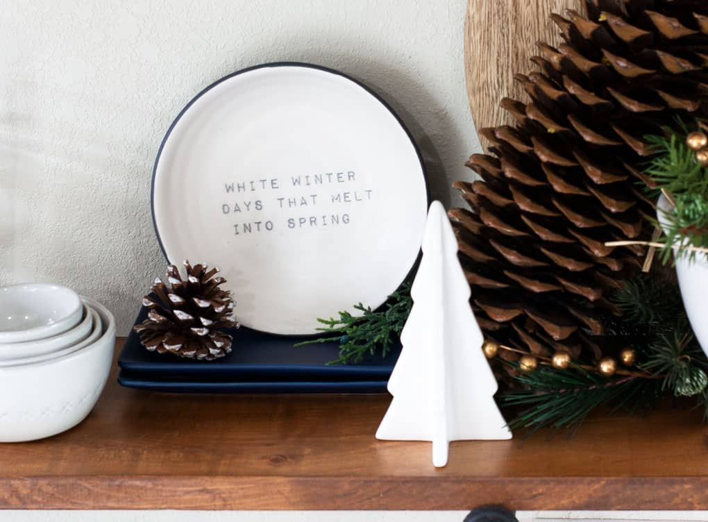 winter-valentine-decor-small-kitchen blue and white dishes with ceramic pine tree and pine cones on wood surface