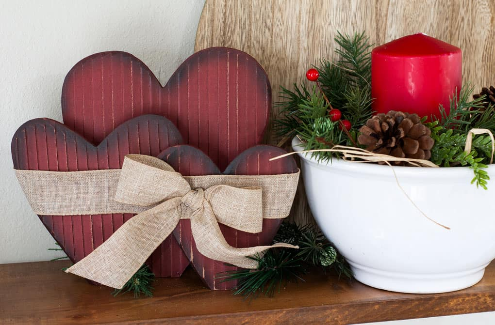 winter-valentine-decor-small-kitchen red wooden hearts and bow wiht white bowl and red candle with greenery and berries on wood surface