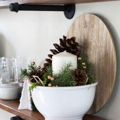 winter-valentine-decor-small-kitchen white dishes on open shelving in a kitchen with white bowl pine cones and candle