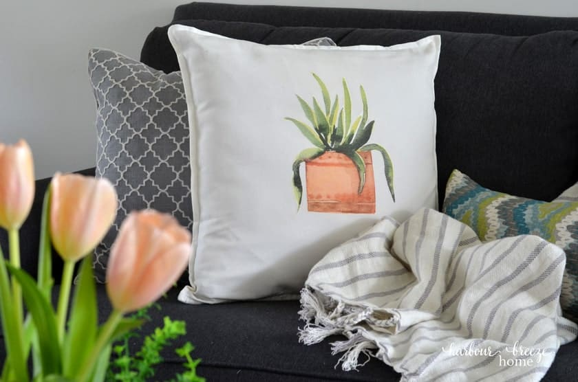 pillow with water color plant graphic on sofa with throw blanket
