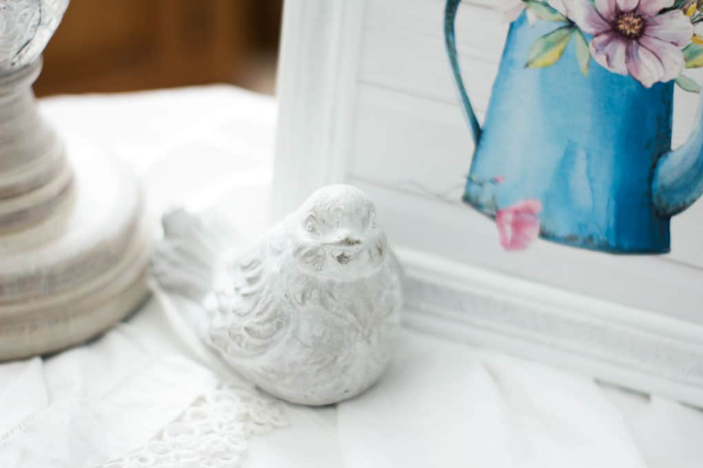 vignette with candle holder and velvet egg and spring printable in frame with bird on linen cloth