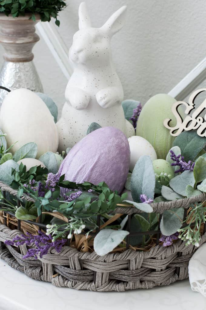 vignette with candle holder and velvet egg with basket bunny lambs ear florals on white surface with window pane in background