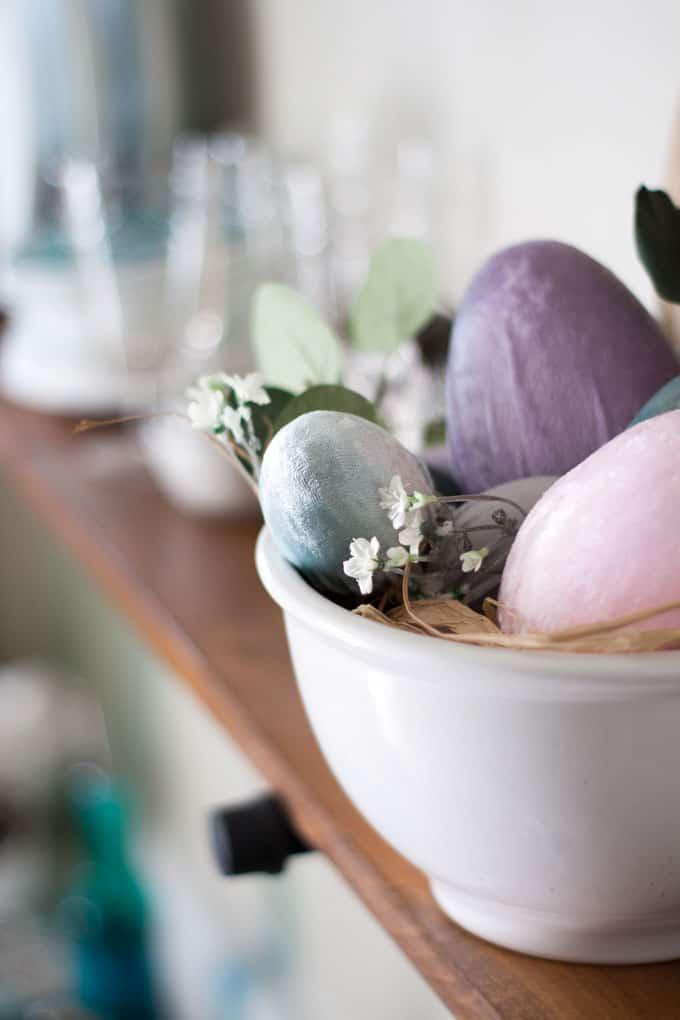 bowl of velvet eggs and faux flower on shelf