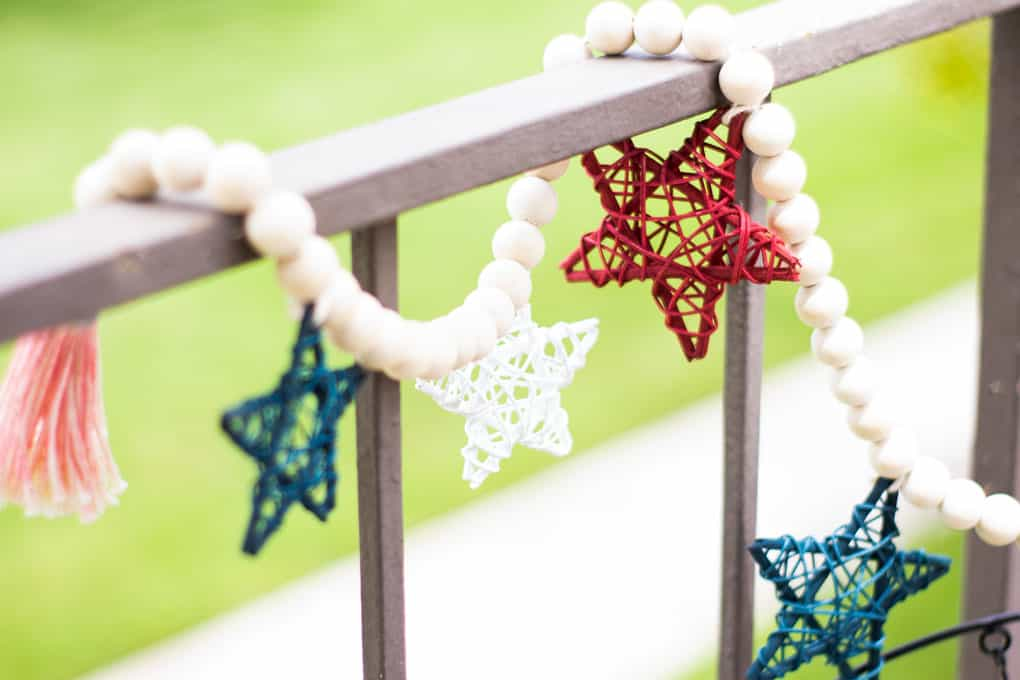 small porch decor red white blue wood bead garland with stars and stair railing outside