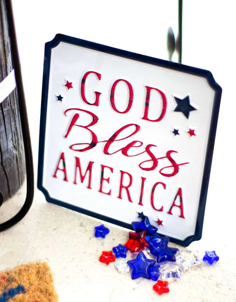 small porch decor red white blue with sign that says God bless America