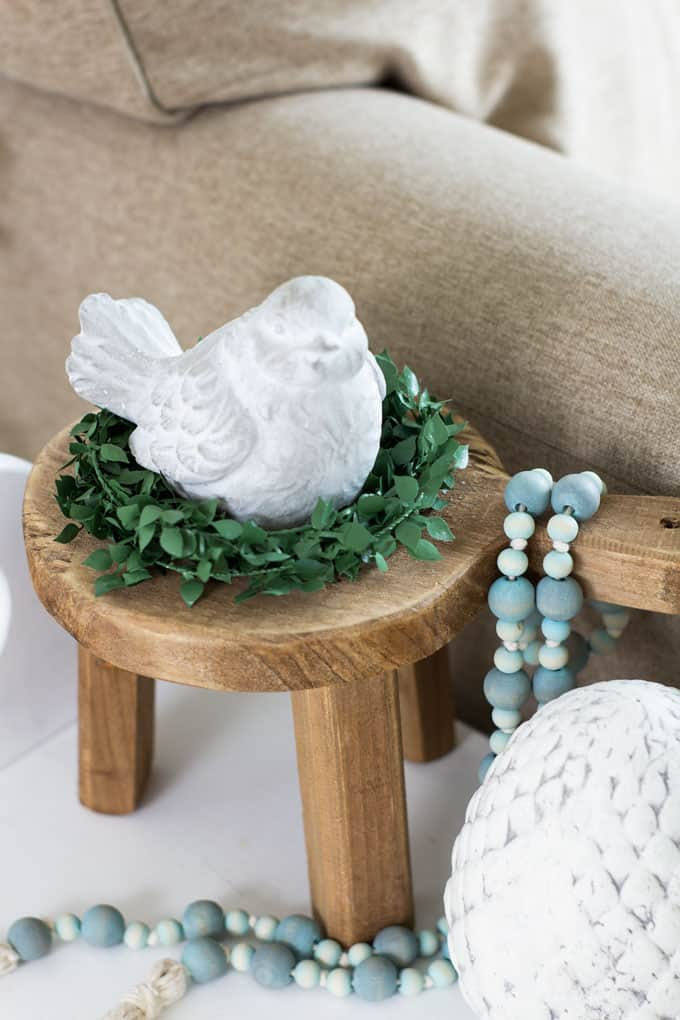 cement bird on mini stool with greenery and beads on table